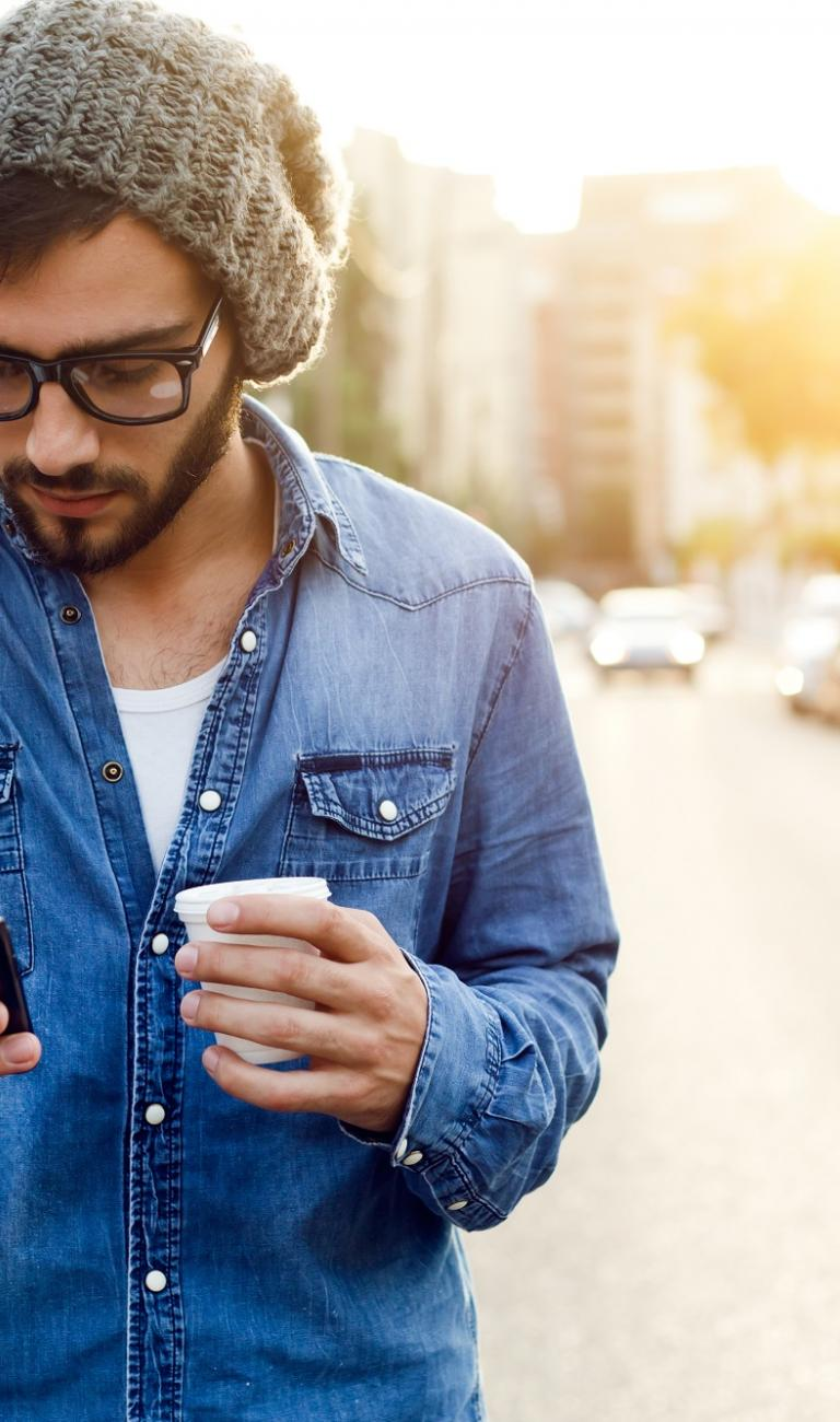 man using a cell phone while holding coffe